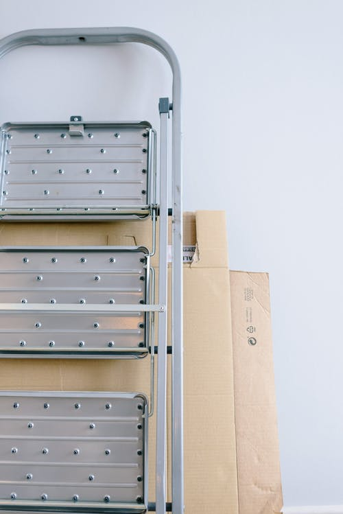 Cardboard boxes and metal ladder in room
