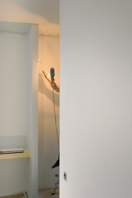 Crop faceless handyman standing on ladder while holding lamp and working in room