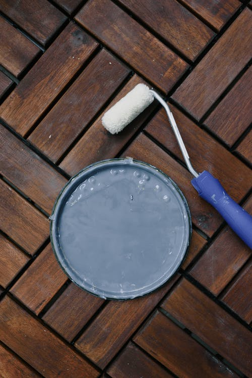 From above of clean paintbrush and plastic cap on wooden floor at home