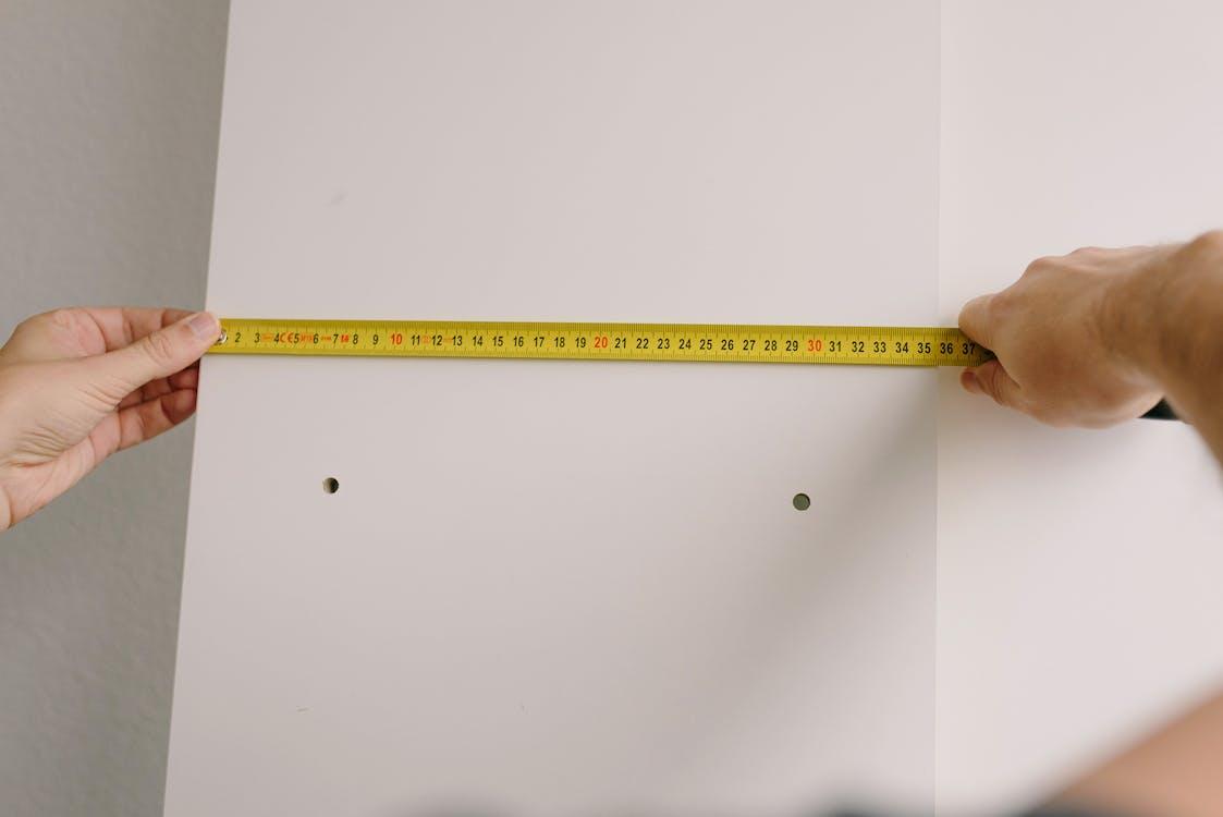 Crop man measuring wooden board in room