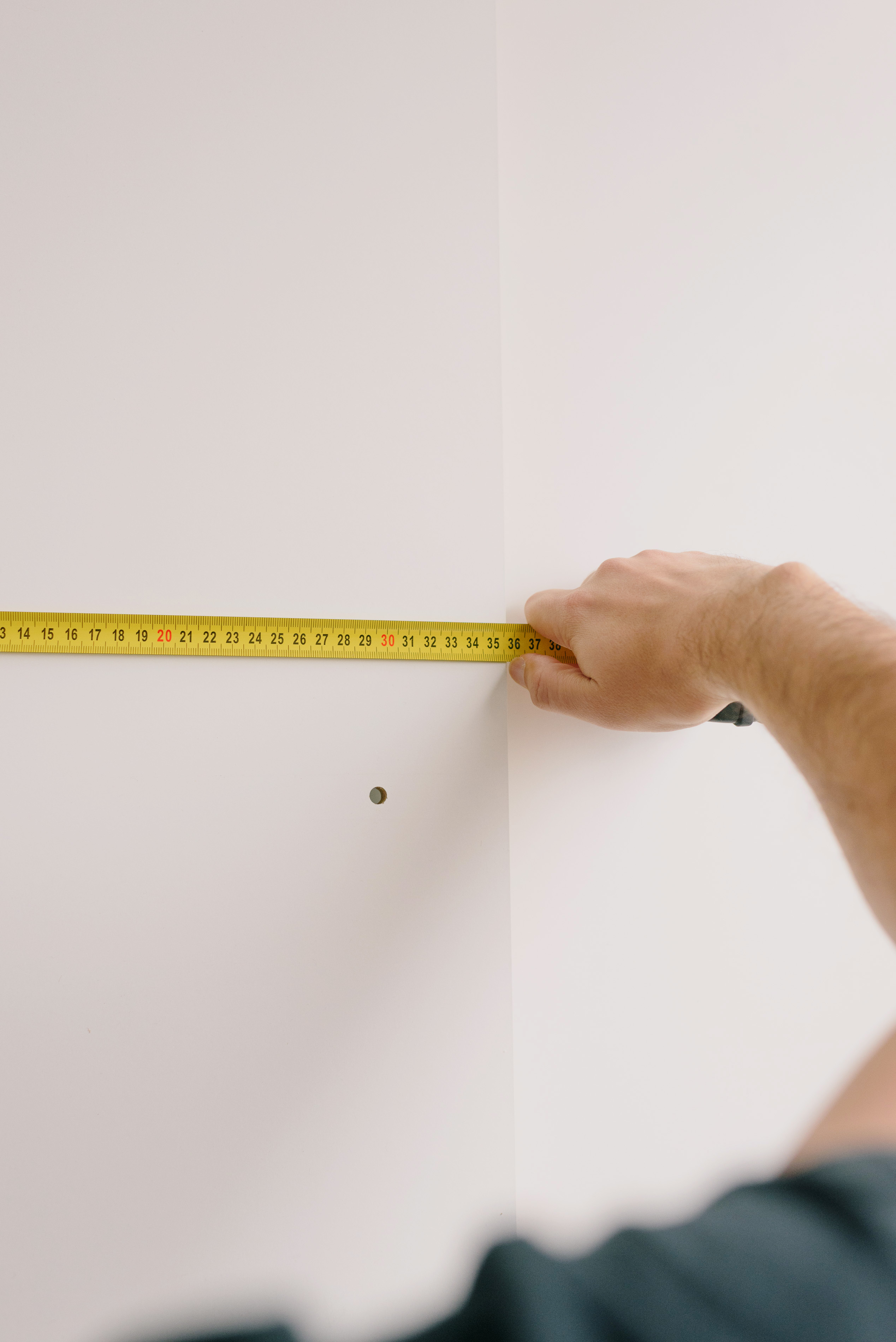 crop man measuring wall at home