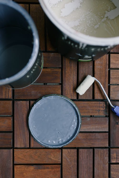 Top view of cans with acrylic paint and clean paint roller on wooden floor at home