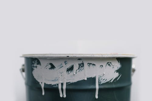 Closeup of white drips from paint on green metal bucket during repair at home