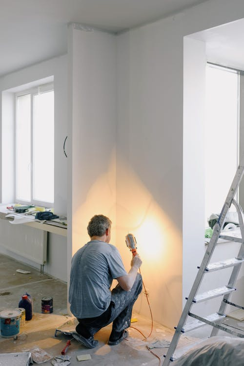 Faceless man working with lamp in room