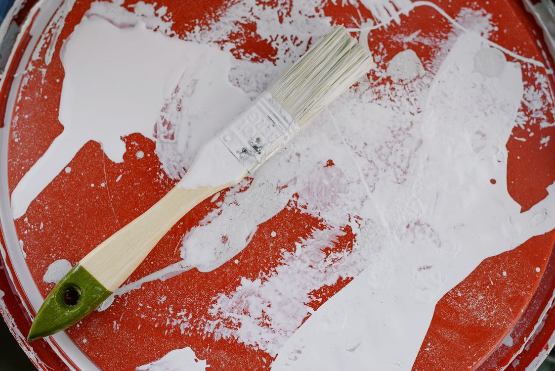 From above of brush with white paint on dirty plastic surface during repair