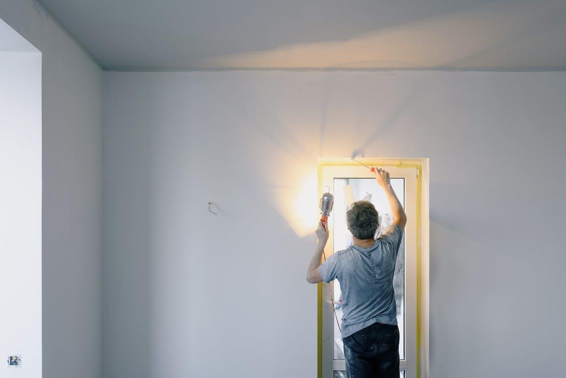 Faceless man repairing door in room