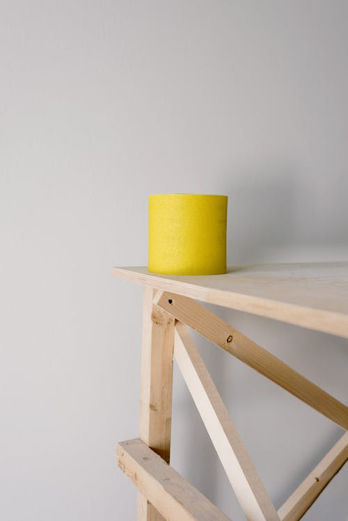 Yellow sandpaper roll placed on wooden scaffold placed in light flat against white wall during renovation