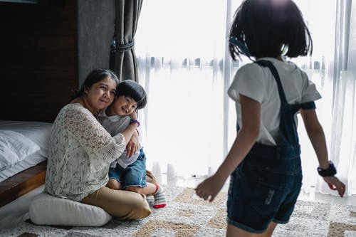 Cheerful mother spending time with children in light room