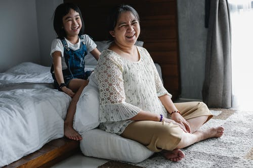 Happy Asian mother resting with daughter at home