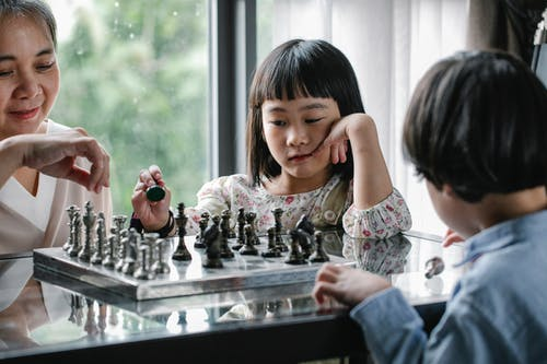 Asian woman playing chess with kids