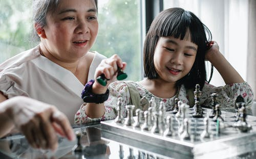 Asian mother playing chess with girl