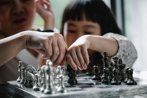 Asian woman and little girl playing chess