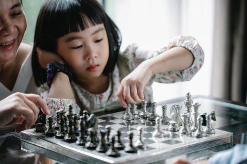 Pensive Asian girl playing chess