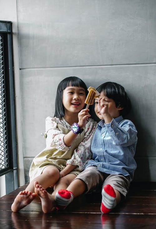 Cute Asian kids clinking ice creams and sitting on floor