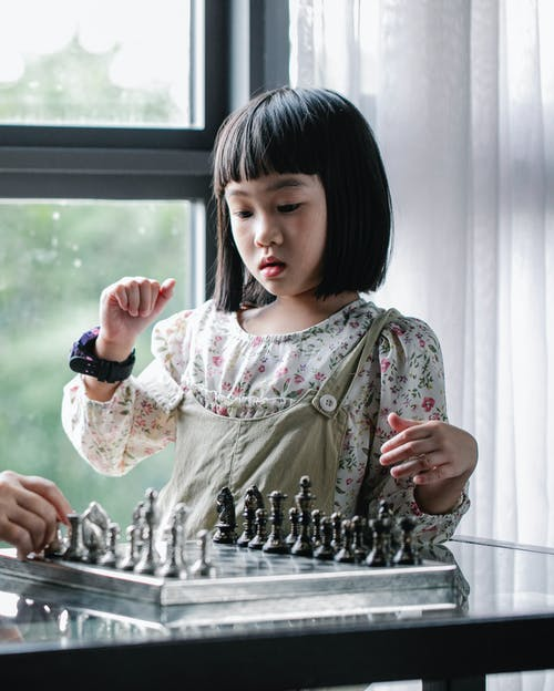 Focused Asian girl playing chess in light room