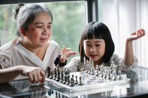 Asian grandmother teaching cute granddaughter to play chess
