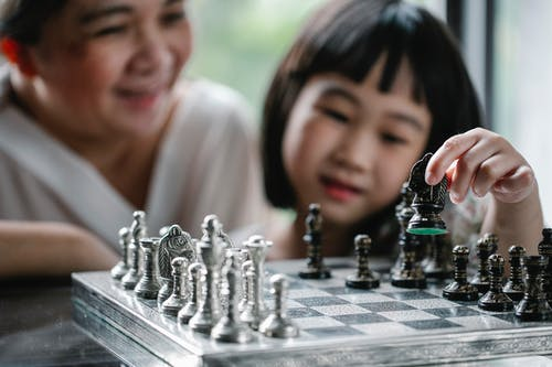 Crop Asian grandmother and girl playing chess together