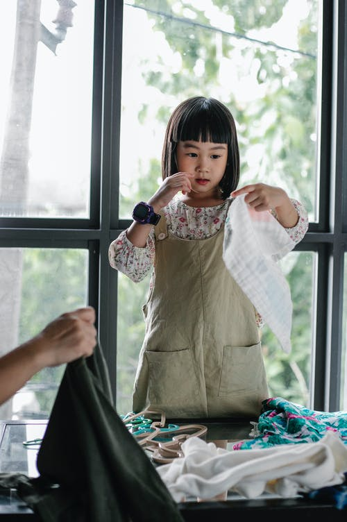 Positive Asian girl choosing clothes heaped on table