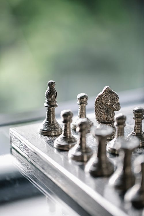 Metal chess pieces on board in room