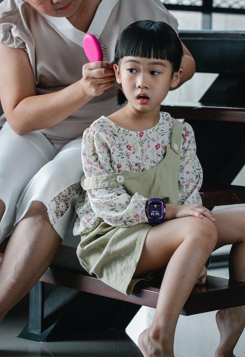 Crop woman brushing hair of little girl