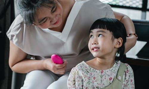 Loving woman brushing hair of little girl