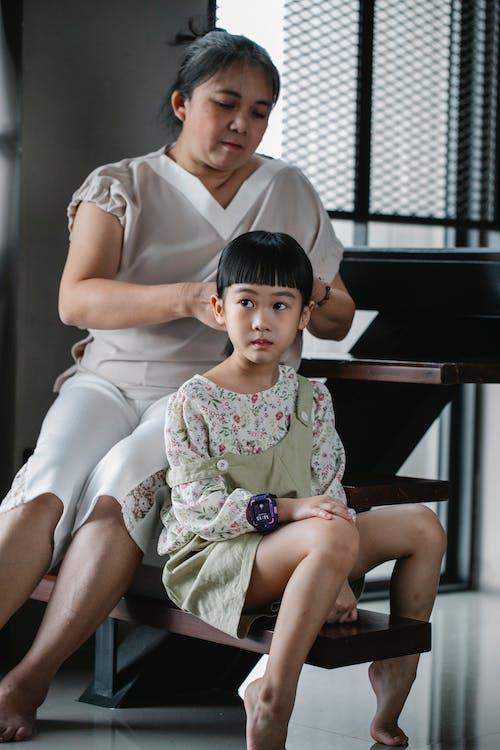 Asian grandmother brushing hair of girl