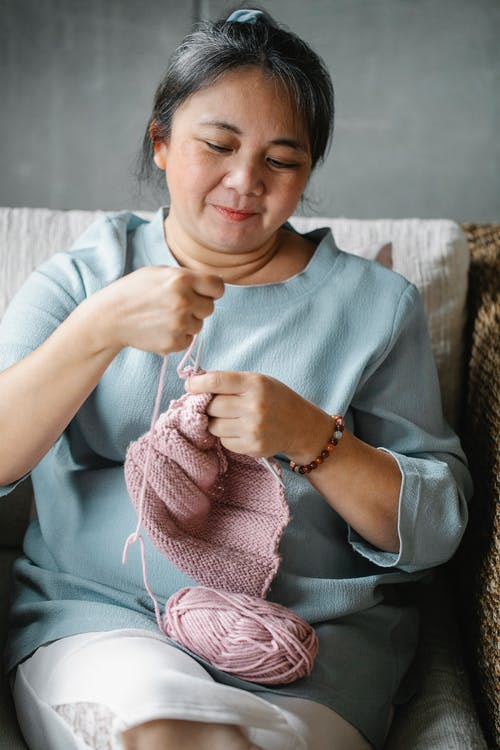 Mature Asian woman sitting in armchair and knitting with pink yarn in leisure
