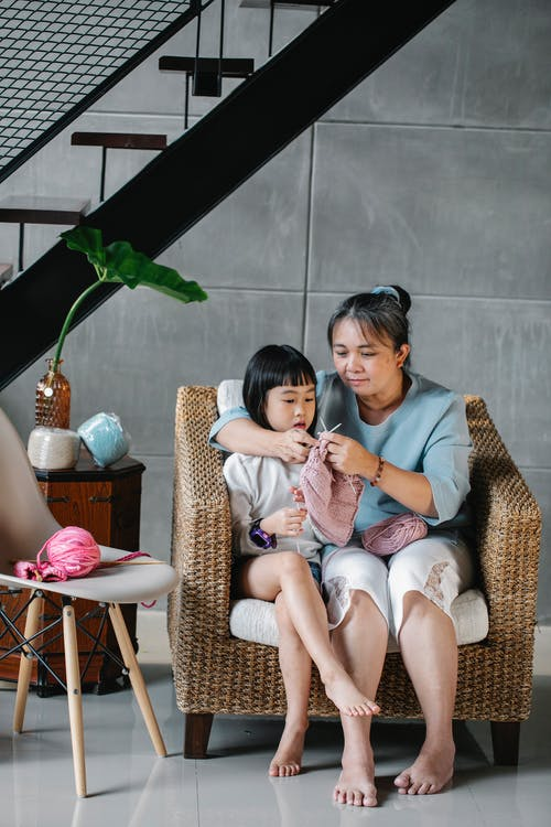 Full body Asian woman with little granddaughter in cozy armchair knitting with pink yarn at home