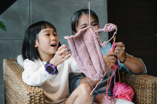 Happy girl and grandmother having fun with knitting