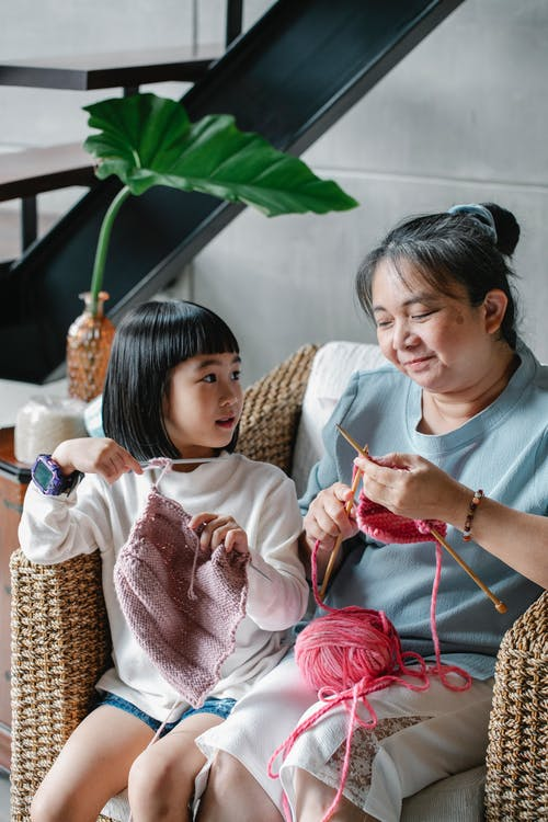Content Asian girl sitting with grandmother in cozy armchair and learning to knit with needles