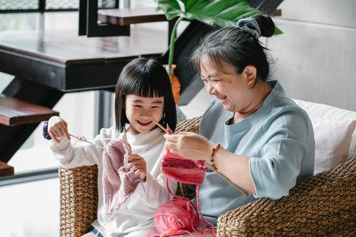 Happy woman and girl knitting at home