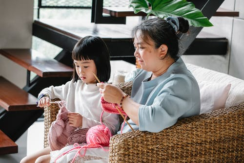 Little Asian girl with mature grandmother sitting in armchair and knitting with needles at home