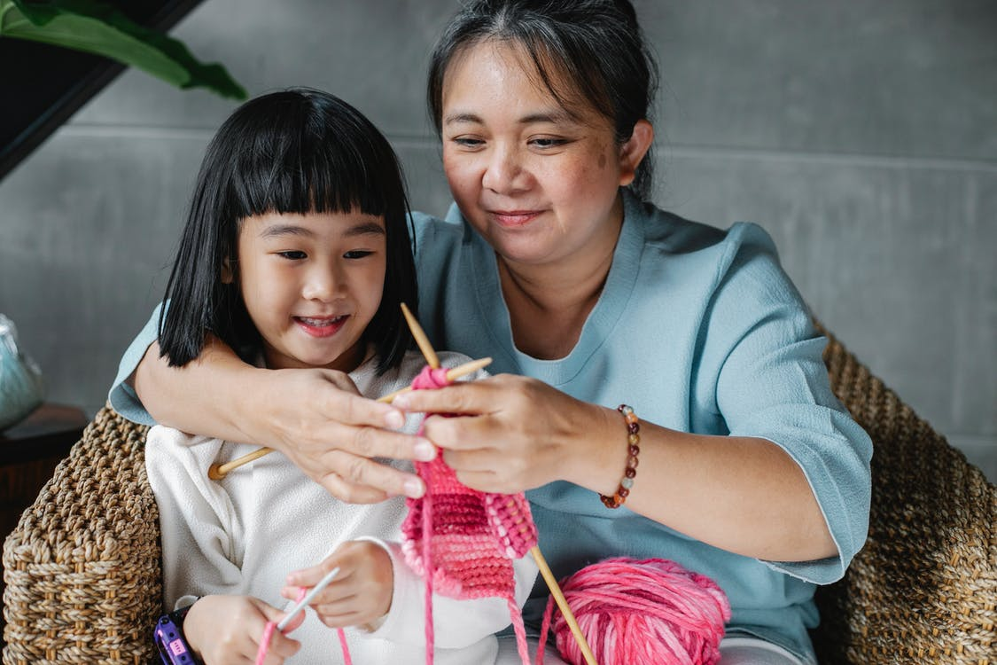 Loving woman with granddaughter knitting