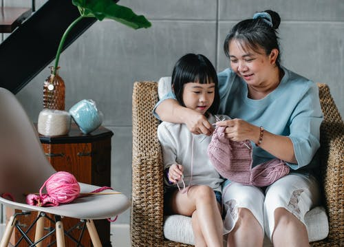 Tender woman with girl knitting at home