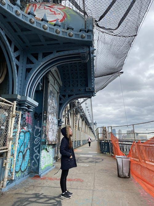 Woman in Black Jacket Walking on Gray Concrete Bridge