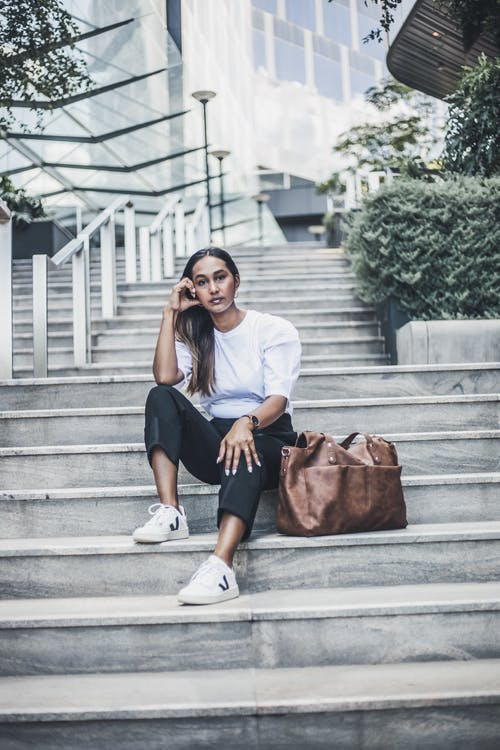Woman in White Shirt and Black Skirt Sitting on Concrete Stairs