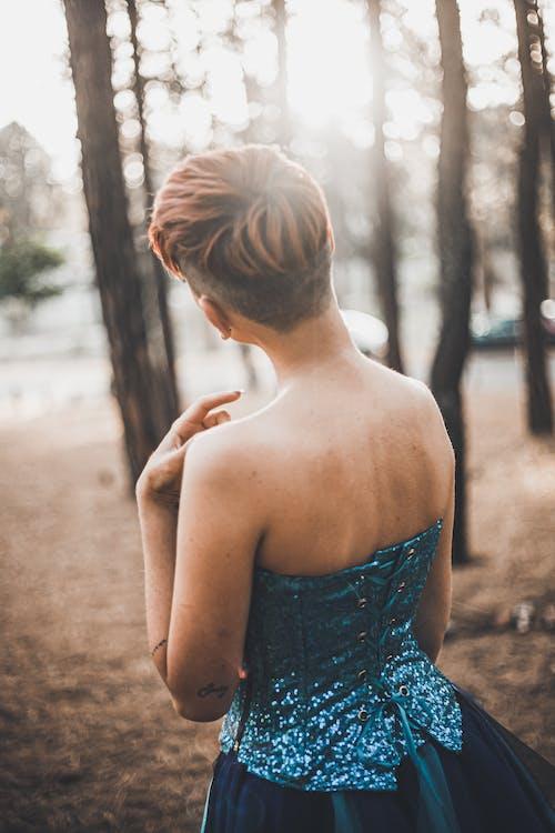 Woman in Blue Tube Dress Standing Near Trees