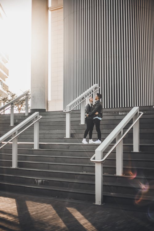 Woman in Black Jacket and Black Pants Walking on Gray Concrete Staircase
