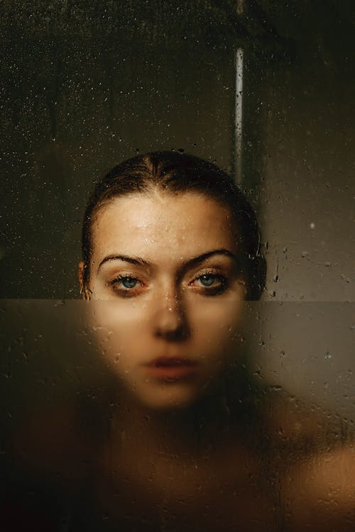Attentive woman behind wet glass wall in shower