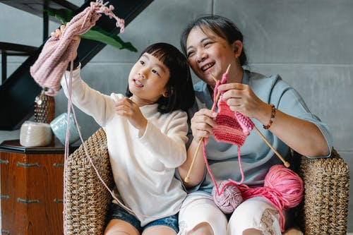 Charming girl with grandmother and knitting
