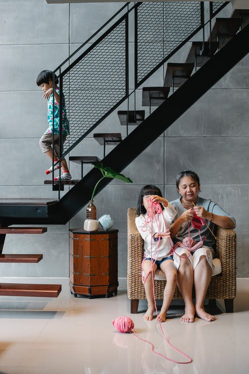 Asian kid going downstairs in villa while sister and grandmother sitting on armchair and knitting