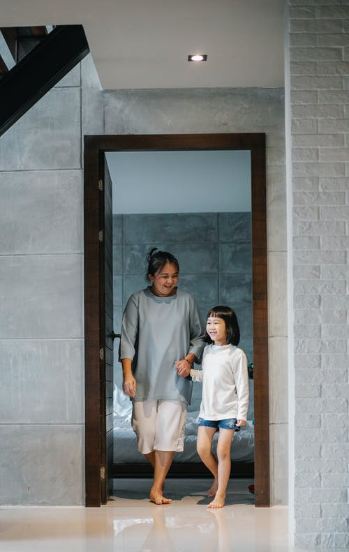 Happy ethnic grandmother with adorable child walking in corridor of modern mansion