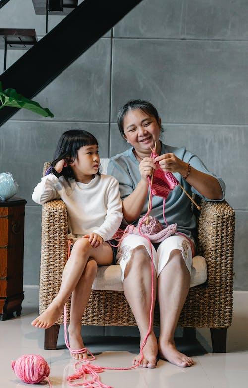 Mujer Asiática Senior Positiva Tejiendo Mientras Está Sentado En Un Sillón Con Linda Nieta