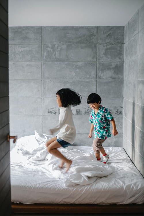 Side view of expressive Asian little children jumping on comfy soft bed while spending time together at home
