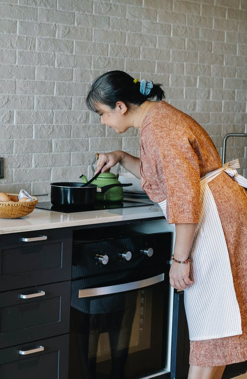 Senior Asian woman cooking dinner in modern kitchen