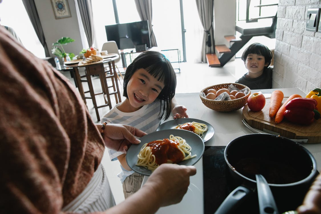 High angle of hungry cute little Asian children smiling while waiting for lunch prepared by unrecognizable grandmother standing in kitchen