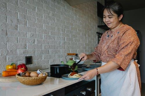Content senior ethnic woman cooking appetizing spaghetti with sauce standing at table with fresh vegetables and eggs in kitchen