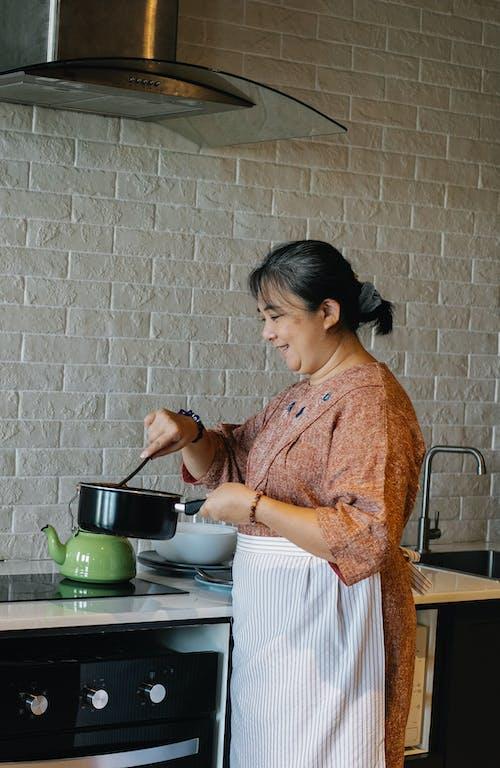 Cheerful senior Asian woman stirring sauce in kitchen