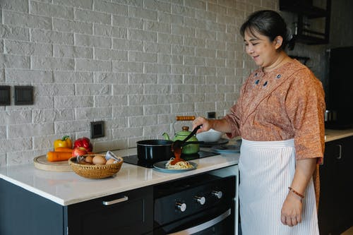 Cheerful senior ethnic housewife pouring sauce on pasta while serving dish in kitchen