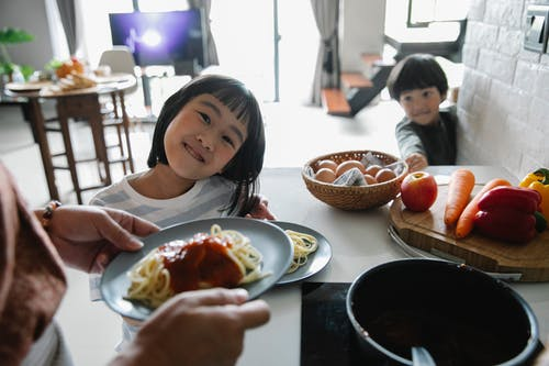 Cheerful cute Asian children waiting for lunch in kitchen